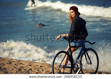 Attractive hipster girl relaxing on the beach after ride on her sport fixed gear bicycle, young woman standing on seashore enjoying sunny afternoon, charming female with rental bike outdoors, filter - stock photo