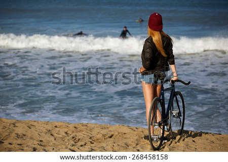 Attractive hipster girl relaxing on the beach after ride on her sport fixed gear bicycle, young woman standing on seashore looking to surfing people in water, charming female with rental bike outdoors - stock photo