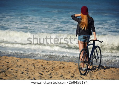 Attractive hipster girl relaxing on the beach after ride on her sport fixed gear bicycle, young woman standing on seashore enjoying sea view at holiday, charming female with rental bike outdoors - stock photo