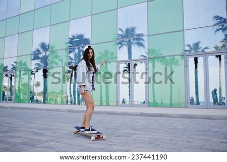 Attractive hipster girl riding on longboard on beautiful background with reflected palm trees in glass of skyscraper, charming young woman looking to the camera while ride a skateboard - stock photo