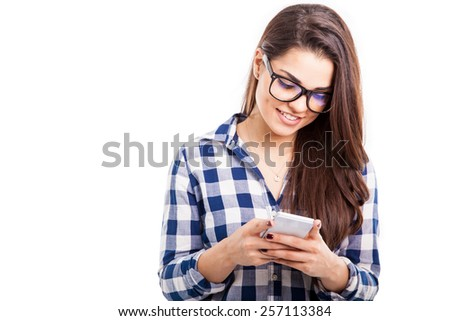 Attractive hipster girl wearing glasses and using her smartphone for texting - stock photo