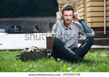 Attractive hipster guy is listening to music from headphones with enjoyment. He is touching them with both his hands. His eyes are closed. He is sitting on grass near backpack - stock photo