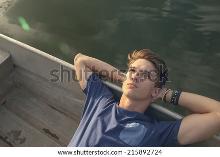 Attractive Hipster Male Relaxing Near River - stock photo