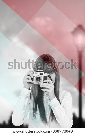 Attractive hipster photographing with camera against colored background - stock photo