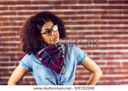 Attractive hipster posing with hands on hips against red brick background - stock photo