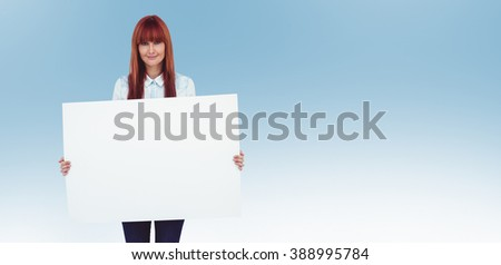 Attractive hipster woman holding white card against blue - stock photo