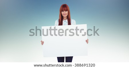 Attractive hipster woman holding white card against dark blue green background - stock photo