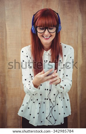 Attractive hipster woman listening to music with headphones against wooden background - stock photo