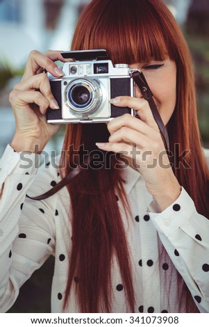 Attractive hipster woman using old fashioned camera in the garden - stock photo
