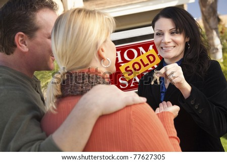 Attractive Hispanic Female Real Estate Agent Handing Over New House Keys to Happy Couple. - stock photo