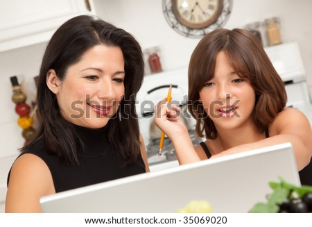 Attractive Hispanic Mother & Daughter in the Kitchen using the Laptop. - stock photo
