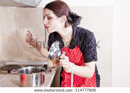 Attractive housewife tasting food - stock photo