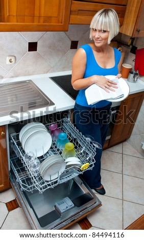 attractive housewife washing dishes in dishwasher in her home kitchen