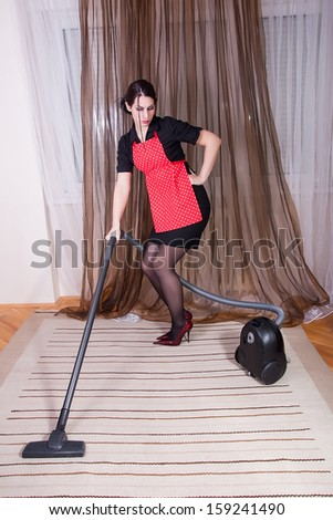 attractive housewife with vacuum cleaner
