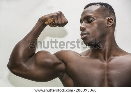 Attractive hunky black male bodybuilder doing bodybuilding pose on white background - stock photo