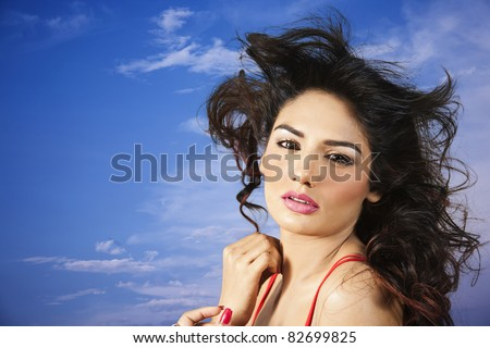 Attractive indian female fashion model with long hair against stormy blue sky with clouds - stock photo