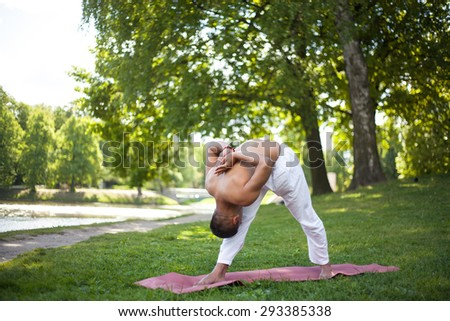 Attractive Indian man in white linen clothes working out on riverbank in park, standing in Intense Side Stretch, Pyramid Pose, Parsvottanasana, hands behind the back in prayer gesture, full length - stock photo