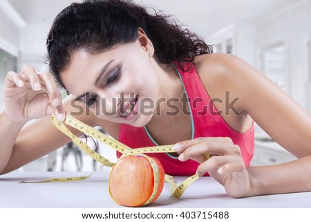 Attractive Indian woman using a measuring tape to measure a fresh apple fruit in the kitchen - stock photo