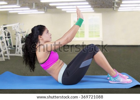 Attractive indian woman workout in the fitness center and doing sit up on the mattress