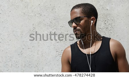 Attractive jogger with muscular athletic body in black sportswear listening to meditative music with earphones standing against gray concrete wall with copy space for your promotional content