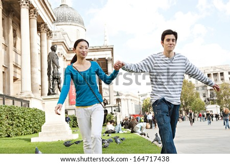 Attractive joyful Japanese tourist couple being playful while walking together holding hands in a landmark of the city of London while on a romantic holiday during a sunny day, outdoors.