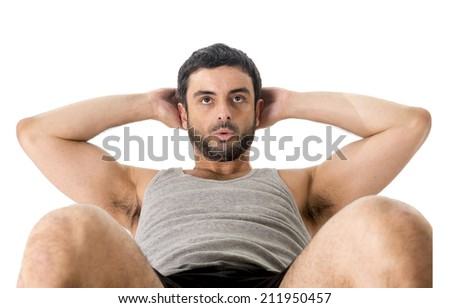attractive latin american sport man wearing running clothes doing a sit up or crunch working this abs isolated on a white background in fitness , body building and healthy lifestyle concept