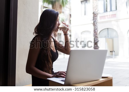 Attractive latin female enjoying her drink while working on net-book in cafe outdoors, young business woman using laptop computer for remote work while sitting in restaurant during coffee break - stock photo
