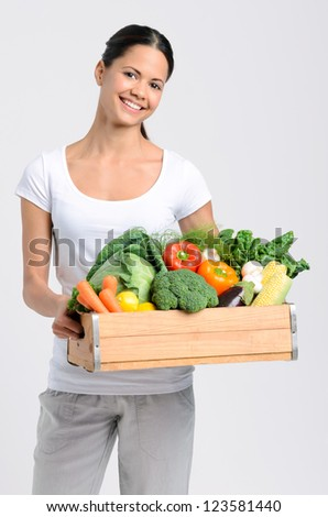Attractive latino woman holding a crate full of fresh organic vegetables on grey background, promoting healthy diet and lifestyle - stock photo