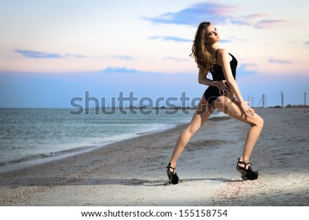 Attractive leggy brunette wearing black swimsuit posing on the beach