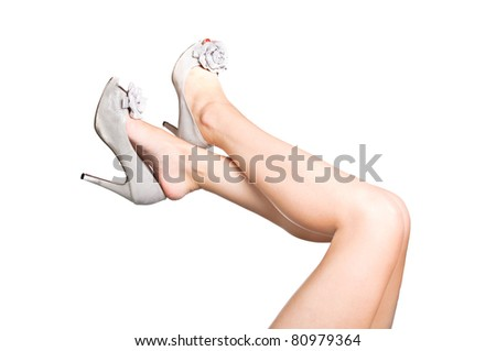 Attractive legs with silver boots, up in the air - stock photo