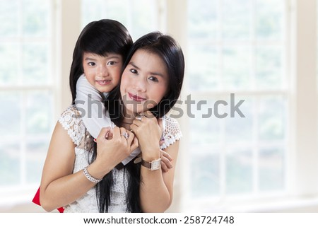 Attractive little girl embrace her mother from the back at home - stock photo