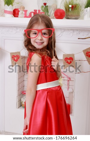 Attractive little girl in red dress over valentine day background on Holiday theme - stock photo