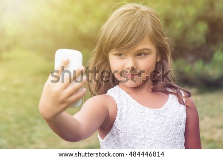 Attractive little girl is doing selfie in summer light. Girl is looking at the smart phone. All potential trademarks are removed.