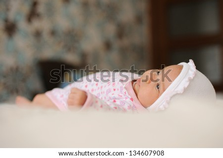 attractive little girl laying on bed - stock photo