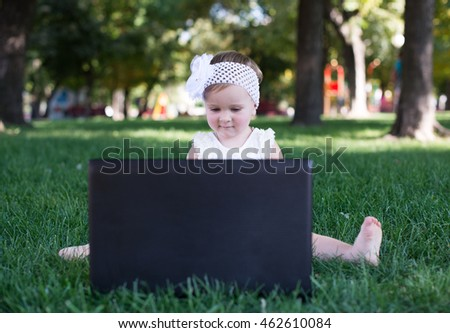 Attractive little girl using laptop in the park lying on the green grass