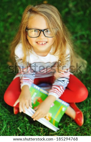 Attractive little girl with book in a park  - stock photo