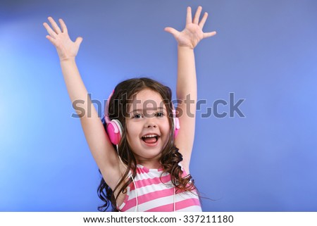 Attractive little girl with pink headphones on blue background