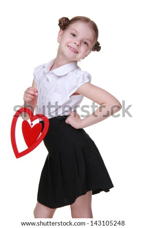 Attractive little schoolgirl with nice hairstyle posing with red wooden heart shape on Holiday theme/Charming schoolgirl wearing white blouse and black skirt and holding red love symbol