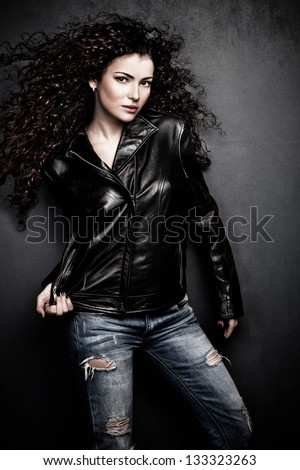 attractive long hair young woman in black leather jacket and blue jeans studio shot small amount of grain added