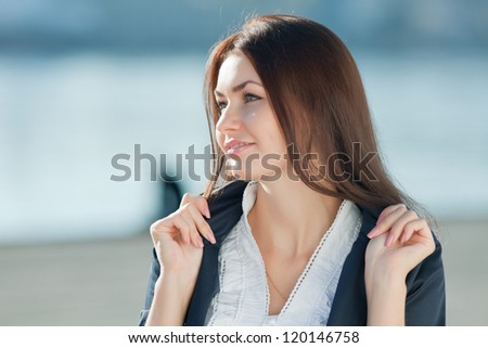 Attractive long haired brunette on open air. Portrait of young businesswoman outdoors - stock photo
