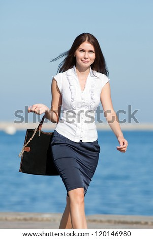 Attractive long haired brunette on open air. Young businesswoman with bag walking along seafront - stock photo
