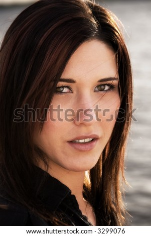 attractive long-haired brunette woman with sunlit highlights in oblique headshot against water background - stock photo