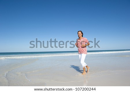 Attractive looking mature woman, keeping fit and healthy, exercising, jogging, running at beach, isolated with ocean and blue sky as background and copy space. - stock photo
