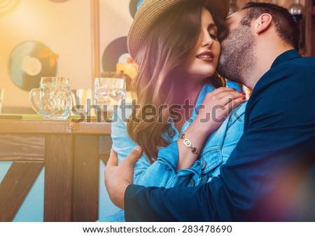 attractive lovers kissing and hugging at bar. horizontal photo