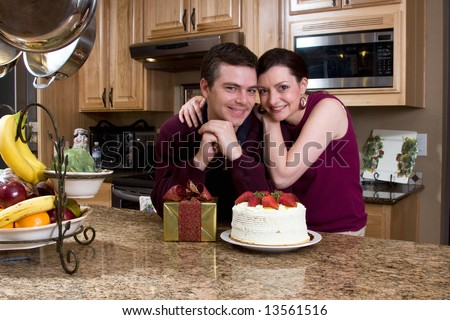 Attractive loving couple hugging and leaning on their kitchen counter which holds a cake and a gift. They are smiling at the camera. - stock photo