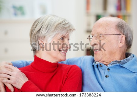 Attractive loving senior couple relaxing at home sitting arm and arm on a sofa in the living room smiling into each others eyes - stock photo