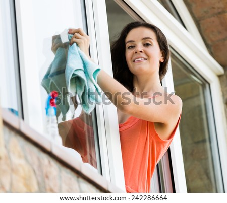 Attractive maid cleaning windows with rag and sprayer in flat - stock photo