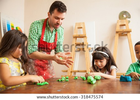 Attractive male art teacher and his students working with some clay for sculpting class - stock photo