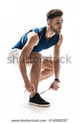 Attractive male athlete is lacing up shoes