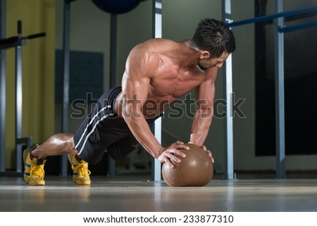 Attractive Male Athlete Performing Push-Ups On Medicine Ball - stock photo